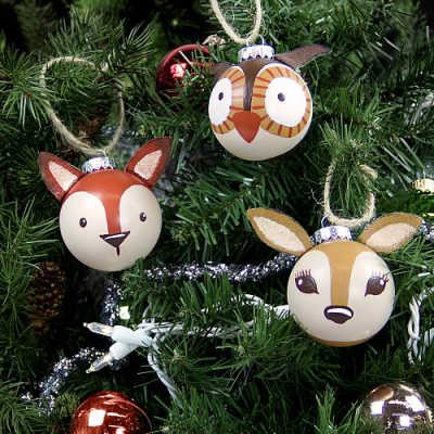 Ornaments shaped like woodland animals hang from a christmas tree