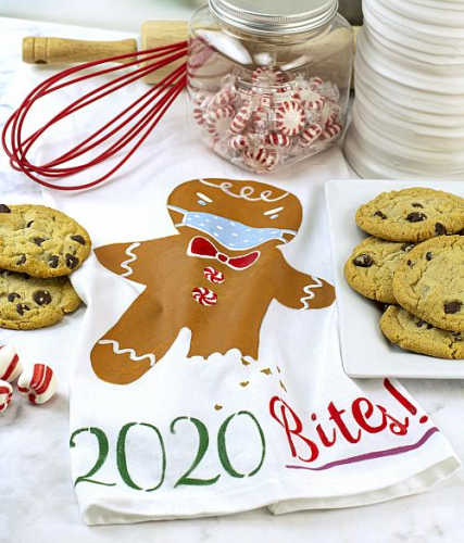 A tea towel with a gingerbread man wearing a face mask that says 2020 bites