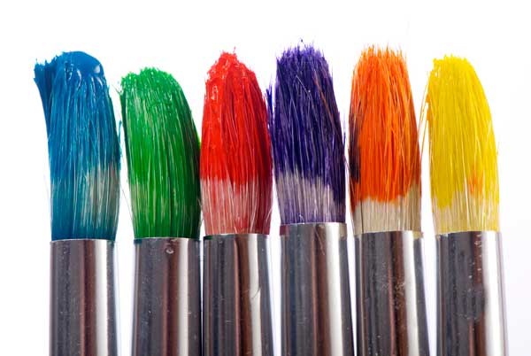 A close-up of the tips of paintbrushes all dipped in paint in order to make a rainbow.