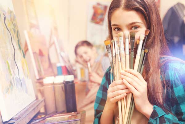 A girl painting on canvas looks towards the camera and holds up and assortment of paintbrushes with a smile.