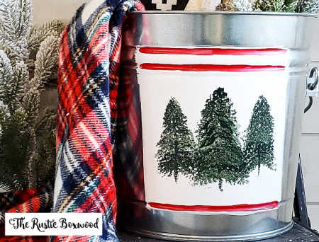 A steel bucket with pine trees painted on it