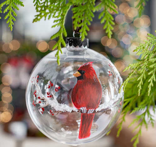 A glass ornament with a red cardinal painted on it sits in a tree