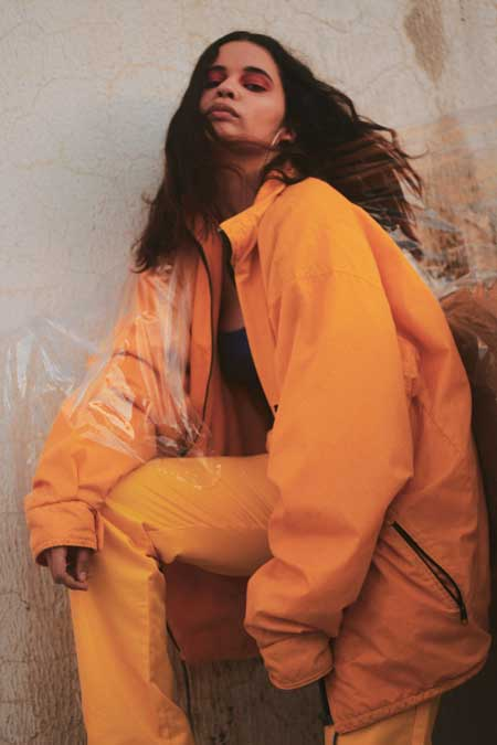 A girl in a marigold yellow tracksuit leans against a wall.