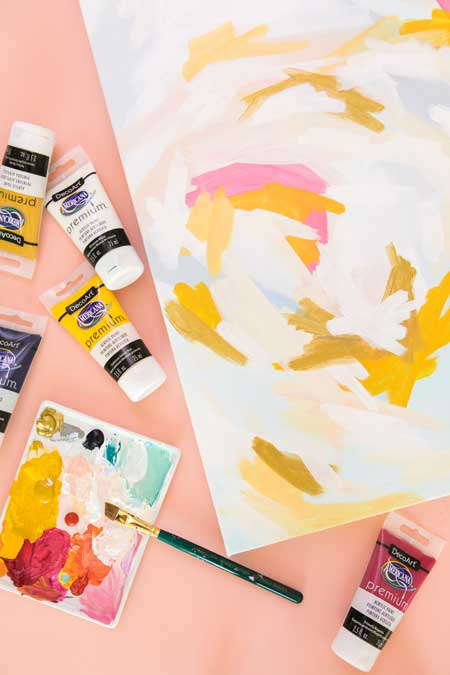 An abstract painting is painted using marigold yellow, white, and pink for a free-form and fun look. Bottles of acrylic paint are scattered around the painting.
