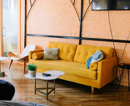 A marigold yellow couch is pushed up against a brick wall in a stylish living room.
