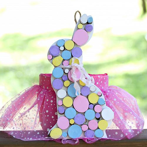 An Easter bunny sign is made out of pastel painted wood slices