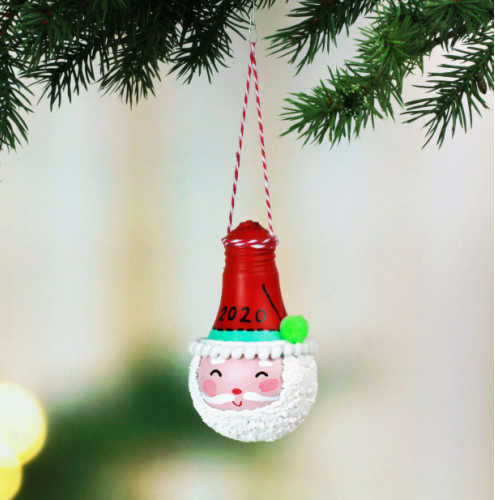 An Santa Claus ornament made from a recycled light bulb hangs off a Christmas tree.