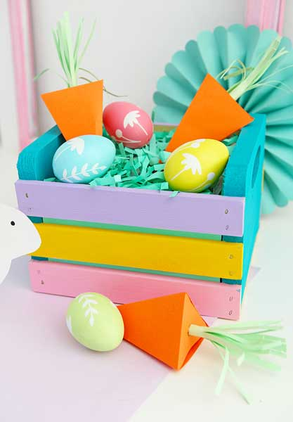 A mini wooden crate is decorated in pastel spring colors and filled with Easter grass