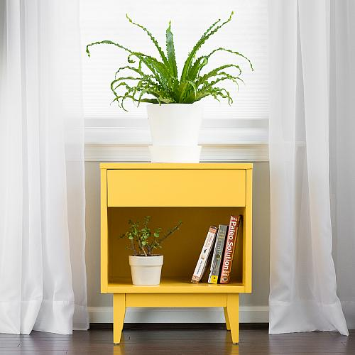 An end table painted in marigold yellow with a potted plant on top of it.