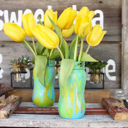 Mason jars are decorated with an acrylic paint pour and filled with yellow tulips as a springtime centerpiece