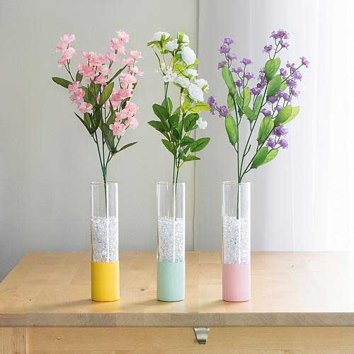 Three tall and thin glass vases are dipped halfway in pastel acrylic paint for a cute spring look