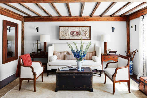 A warm white room with natural wood beams